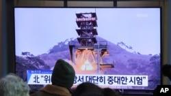 Ljudi gledaju preko televizije fotografi zemaljskog testa motora u Severnoj Koreji, na železničkoj stanici u Seulu, Južna Koreja, 9. decembra 2019.