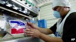 """Roberto Evora, un empleado de """"La Canasta"""", fabricantes de especias secas y bebidas en polvo, sella una bolsa de un producto que se exportará al mercado estadounidense en Santa Tecla, El Salvador, el jueves 5 de mayo de 2005."""