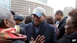 FILE - Former Massachusetts Gov. Deval Patrick, center, greets people in a crowd in Boston, April 2, 2018.