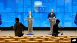 Photographers move around in a nearly empty press room as European Council President Charles Michel, right, and European Commission President Ursula von der Leyen, left, speak after a video-conference with G7 leaders at the European Council building…