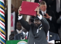 FILE PHOTO - In this photo taken on July 09, 2011, the President of South Sudan Salva Kiir waves the newly signed constitution of his country for the crowd to see during a ceremony in the capital Juba to celebrate South Sudan's independence.