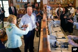 President Joe Biden hands ice cream to Sen. Tammy Baldwin, D-Wis., during a stop at The Pearl Ice Cream Parlor, June 29, 2021, in La Crosse, Wis.