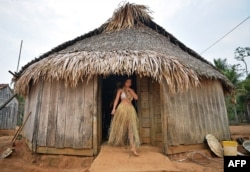 A young woman from the Uru Eu Wau Wau tribe leaves a straw-thatched hut in the tribe's reserve in the Amazon, south of Porto Velho, Brazil, Aug. 29, 2019.