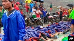 People gather near the bodies of victims of a landslide near a jade mining area in Hpakant, Kachine state, northern Myanmar Thursday, July 2, 2020.