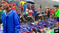 People gather near the bodies of victims of a landslide near a jade mining area in Hpakant, Kachine state, northern Myanmar Thursday, July 2, 2020. Myanmar government says a landslide at a jade mine has killed dozens of people. (AP Photo/Zaw Moe…