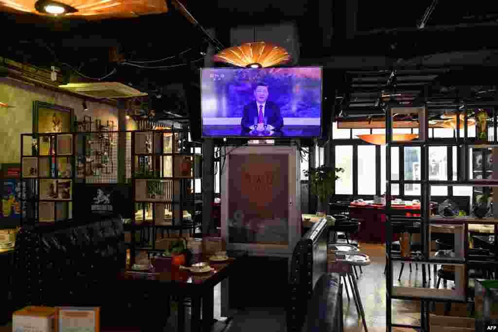 """중국 베이징의 한 텅빈 식당 TV 화면에 말레이시아에서 화상으로 진행되는 시진핑 국가주석의 '아시아태평양경제 협력체(APEC) CEO 대화' 연설이 중계되고 있다. 시 주석은 연설에서 중국의 대외 """"개방의 문은 더 넓어질 것""""이라고 밝혔다."""