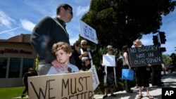 FILE - This April 28, 2019, file photo shows Kyle Fox holding a sign with his father Brady Fox in support of the victims of Chabad of Poway synagogue shooting in Poway, Calif. California's attorney general says the number of reported hate crimes and…