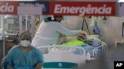 Para petugas kesehatan merawat seorang pasien COVID-19 di unit gawat darurat di rumah sakit lapangan khusus COVID-19 di Ribeirao Pires, Sao Paulo, Brazil, 13 April 2021.