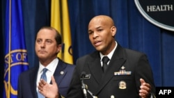 U.S. Surgeon General, Vice Admiral Jerome Adams, flanked by Health and Human Services Secretary Alex Azar, briefs the media on the release of a warning against marijuana use by by adolescents and pregnant women, in Washington, Aug. 29, 2019.