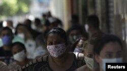 27일 브라질 리우데자네이루에서 시민들이 신종 코로나바이러스 감염증(COVID-19) 대책으로 마련된 정부 보조지원금을 받기 위해 은행 앞에 서 있다.