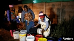 FILE - Residents collect water at night from an electric-powered well, as the country faces 18-hour daily power cuts, in a suburb of Harare, Zimbabwe, July 30, 2019.