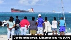 Des Mauriciens regardent le vraquier MV Wakashio échoué près du parc marin de Blue Bay dans le sud-est de l'île Maurice le 6 août 2020.