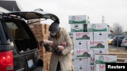 A woman holds goods as Forgotten Harvest food bank distributes goods ahead of Christmas, amid the coronavirus disease (COVID-19) pandemic in Warren, Michigan, Dec. 21, 2020.