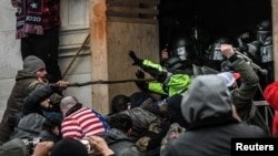 """Los partidarios del presidente de los Estados Unidos, Donald Trump, se enfrentan a la policía en la entrada oeste del Capitolio durante una protesta """"Stop the Steal"""" frente al edificio del Capitolio en Washington DC, el 6 de enero de 2021."""
