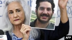 FILE - Debra Tice, mother of U.S. journalist Austin Tice, who was kidnapped in Syria five years prior, holds a dated portrait of him during a press conference in the Lebanese capital, Beirut, on July 20, 2017.