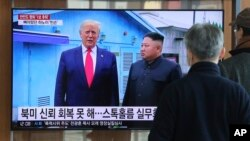 FILE - People watch a TV screen showing a file image of North Korean leader Kim Jong Un and U.S. President Donald Trump, left, during a news program at the Seoul Railway Station in Seoul, South Korea, Dec. 31, 2019.