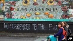 FILE - People walk past pro-Brexit graffiti in West Belfast Northern Ireland, Oct. 14, 2019.