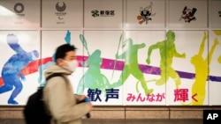 فیس ماسک پہنے ہوئے ایک شخص شن جوکو سٹی ہال سے گزر رہا ہے جہاں پس منظر میں اولمپکس کا ایک پوسٹر لگا ہے۔ 29 جنوری 2021