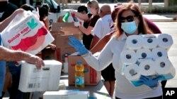 ضرورت مندوں کی امداد کے لیے لگائے گئے کیمپ میں لوگ سامان کے عطیات دے رہے ہیں۔ فائل فوٹو