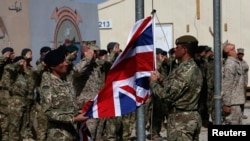 FILE - British troops lower the Union flag during a ceremony marking the end of operations for U.S. Marines and British combat troops in Helmand, Afghanistan, Oct. 26, 2014.
