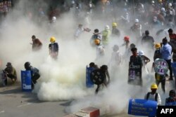 Los manifestantes reaccionan después de que la policía lanzara gases lacrimógenos durante una manifestación contra el golpe militar en la ciudad noroccidental de Kalay, el 2 de marzo de 2021.