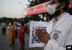 Para dokter memberi penghormatak kepada tentara India yang tewas dalam kontak senjata dengan tentara China di wilayah Ladakh, sambil memegang foto mereka, di New Delhi, India,18 Juni 2020.