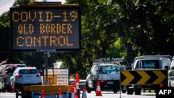 A COVID-19 signage is seen at a vehicle checkpoint on the Pacific Highway on the Queensland - New South Wales border in Brisbane on April 15, 2020. - A state border that bisects Australia's neighbouring beachside towns of Coolangatta and Tweed…