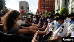 Manifestantes realizan gestos de pacifismo frente a los agentes policiales durante las protestas en Guatemala, el 28 de noviembre de 2020.