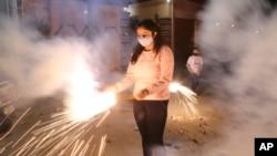 Seorang anak perempuan bermain kembang api dalam perayaan festival cahaya, Diwali, di Jammu, India, Sabtu, 14 November 2020.