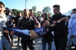 FILE - A wounded protester is evacuated during a demonstration to denounce then-President Abdelaziz Bouteflika's bid for a fifth term, in Algiers, Algeria, Feb. 23, 2019.
