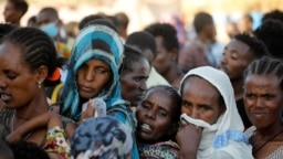 FILE - Ethiopian refugees line up for supplies at the Um Rakouba refugee camp, which houses refugees fleeing the fighting in the Tigray region, on the Sudan-Ethiopia border in Sudan, Nov. 29, 2020.