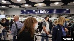 FILE - Arriving passengers queue at UK Border Control at Terminal 5 at Heathrow Airport in London, Britain, June 29, 2021.