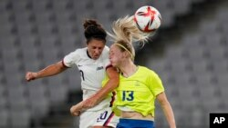 United States' Carli Lloyd, left, and Sweden's Amanda Ilestedt, right, go for a header during a women's soccer match at the 2020 Summer Olympics, July 21, 2021, in Tokyo.