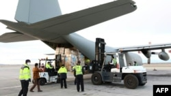 A handout picture released by the World Health Organization (WHO) on March 2, 2020, shows the unloading of medical equipment and coronavirus testing kits upon their arrival at Mehrabad International Airport in Iran's capital Tehran.
