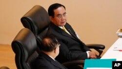 泰國總理巴育(上圖)在議會特別會議上與副總理巴威交談。(2020年10月26日)