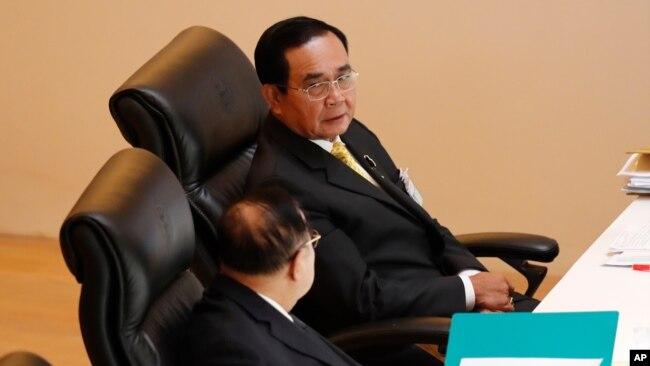 泰国总理巴育(上图)在议会特别会议上与副总理巴威交谈。(2020年10月26日)