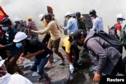 Gas air mata dan gas pemadam kebakaran mengelilingi para demonstran saat mereka melarikan diri dari polisi saat melakukan protes terhadap kudeta militer di Naypyitaw, Myanmar, 8 Maret 2021. (Foto: Reuters)