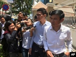 Journalist Yeang Sothearin, second from right, speaks to reporters as he and co-accused Uon Chhin leave municipal court in Phnom Penh, Cambodia, July 26, 2019.