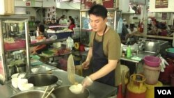 """Alex Lee runs a wonton noodle stall at a popular open-air food court in Kuala Lumpur. Lee, a smoker for two decades, supports enforcement of the smoking ban at all eateries nationwide. """"People should have clean air while they eat,"""" he says."""