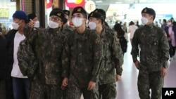 Soldados surcoreanos con mascarilla para protegerse del coronavirus abordan un tren en Seúl, el 3 de noviembre de 2020.