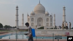 A man disinfects the premises of the Taj Mahal monument that was reopened after being closed for more than six months due to the coronavirus pandemic in Agra, India, Monday, Sept.21, 2020. (AP Photo/Pawan Sharma)