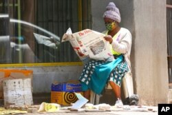 """FILE - A masked vendor reads a newspaper in Harare, Jan,5, 2021. At the time, Zimbabwe began a 30-day lockdown to rein in a spike in COVID-19 infections. On Feb. 12, 2021, the government said a free COVID-19 vaccination program would begin """"immediately."""""""