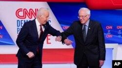 미국 대선 민주당 후보 경선 주자 조 바이든 전 부통령과 버니 샌더스 상원의원이 지난 3월 워싱턴 CNN 스튜디오에서 열린 첫 양자 TV토론에서 팔꿈치 인사를 나누고 있다.