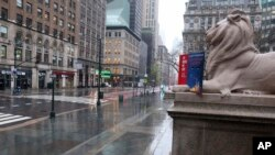 Fifth Avenue in front of the New York Public Library is empty on a rainy day in New York, Monday, April 13, 2020.