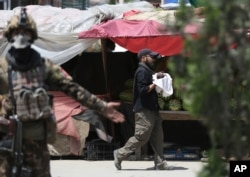 AAn Afghan security officer carries a baby after gunmen attacked a maternity hospital, in Kabul, Afghanistan, May 12, 2020