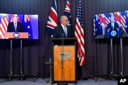 Australia's Prime Minister Scott Morrison, center, appears on stage with video links to Britain's Prime Minister Boris Johnson, left, and U.S. President Joe Biden at a joint press conference at Parliament House in Canberra, Sept. 16, 2021.