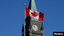 FILE - A Canadian flag flies in front of the Peace Tower on Parliament Hill in Ottawa, Ontario, March 22, 2017.