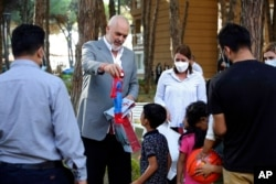 Albanian Prime Minister Edi Rama offers a gift to a boy during his visit to a resort accommodating Afghan refugees in Golem, west of Tirana, Aug. 27, 2021.