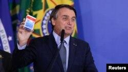 El presidente Jair Bolsonaro habla en la ceremonia de inauguración de Eduardo Pazuello como ministro de Salud mientras sostiene una caja de hidroxicloroquina, el 16 de septiembre de 2020.