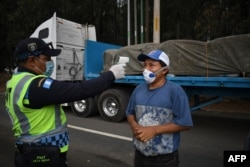 A transit police officer checks the temperature of a truck driver as a preventive measure against the new coronavirus, during a partial curfew ordered by the government in Villa Nueva, Guatemala, on April 2, 2020.